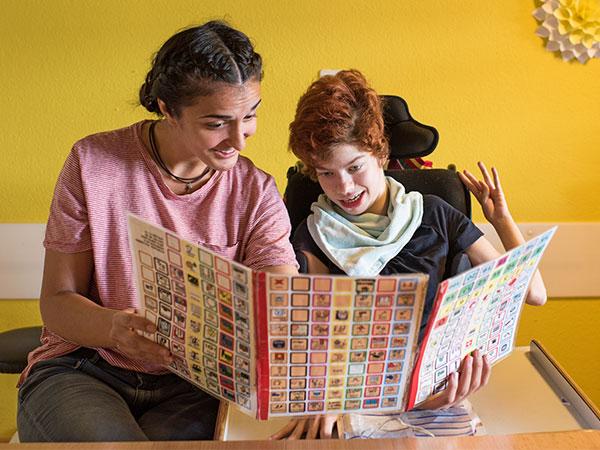 Bild einer Mitarbeiterin im Gespräch mit einer Klientin mithilfe von Unterstützter Kommunikation