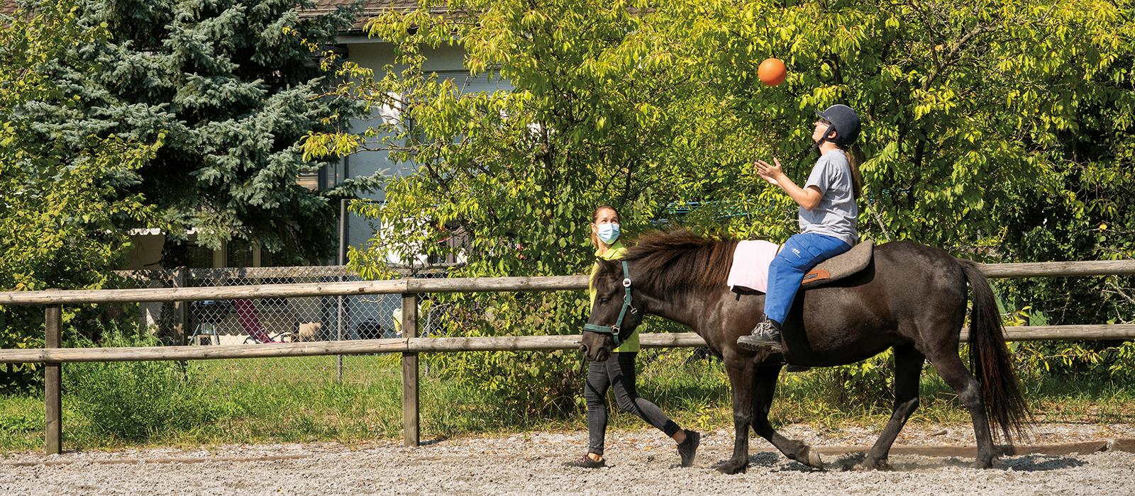 Übung mit Ball im Heilpädagogischen Reiten