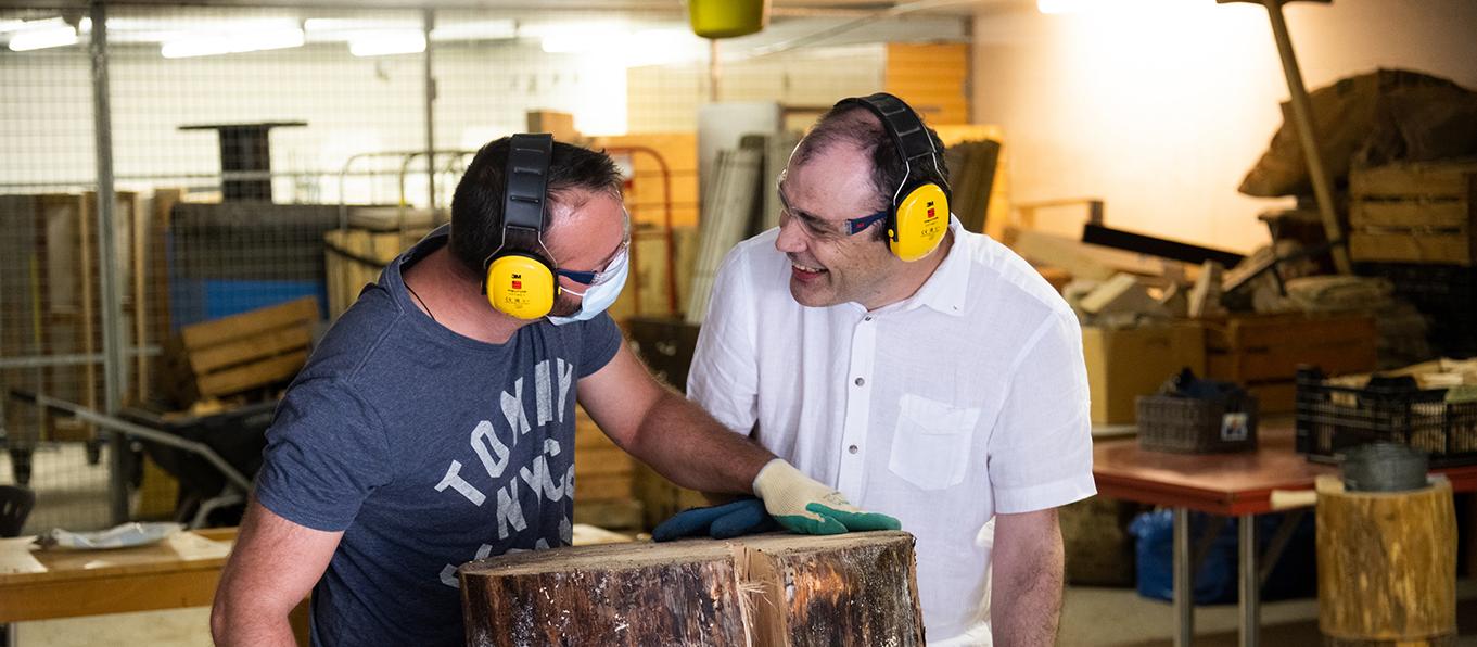 Betreuer und Bewohner beim Holz sägen