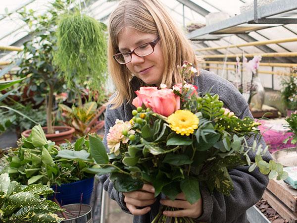Bild einer Mitarbeiterin mit Blumenstrauss
