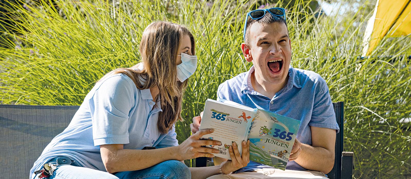 Ein Bewohner und eine Bewohnerin schauen ein Buch an